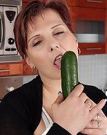Horny mature slides cucumber into her shaved vagina