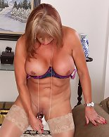 Playful mature woman plays with large stiff dildo